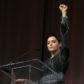 Rose McGowan raise fist speech on stage podium